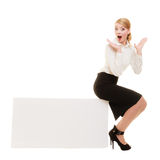 Ad. Businesswoman sitting on blank copy space banner. Advertisement. Surprised young woman sitting on blank copy space banner isolated on white. Businesswoman Stock Image