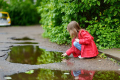 Ad girl playing in a puddle on rainy summer day Royalty Free Stock Image