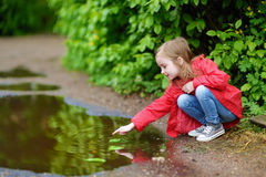 Ad girl playing in a puddle on rainy summer day Stock Photo