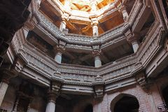 Adalaj Stepwell, Ahmedabad, Gujarat, India. Adalaj stepwell is five stories deep. Upper storeys with intricate stone carvings on pillars, pilaster and Stock Photos