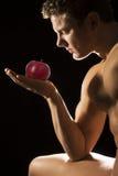 Adam, das einen Apfel betrachtet Lizenzfreie Stockbilder
