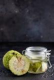 Adam-` s Apfel auf einem schwarzen Hintergrund Tinktur von Adam-` s Apfel in einem Glasgefäß Lizenzfreies Stockfoto