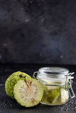 Adam`s apple on a black background. Tincture of Adam`s apple in a glass jar. Royalty Free Stock Photography