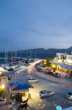 Adamas Milos Greek island town. Adamas Milos Cyclades Greek island town at dusk waterfront harbor yachts and landscape scenery vertical composition Royalty Free Stock Photos