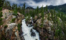 Adams Falls Panorama. Adams Falls on a cloudy day with mountains and trees in the background along the East Inlet Trail of Rocky Mountain National Park, Colorado stock photography