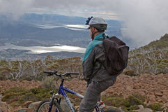 Adams field, Tasmania-November 08, 2005: Mountainbikers view ove. R the lake of Adamsfield. The bike tour goes trough eucalyptus forest Stock Photography