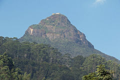 Adams Peak. On an early spring morning, with a cloudless blue sky around it. Sri Pada - sacred footprint refers to the rock formation at the summit stock image