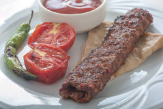 Adana Kebab. Close up of a plate of Turkish adana kebap served with grilled tomatoes and green peppers on flat bread Stock Photos