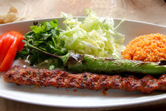 Adana Kebab with dressing. Plate of Adana Kebab a typical turkish meat dish Stock Photography