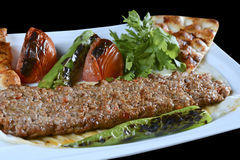 Adana kebab. ı is a long, hand-minced meat kebab mounted on a wide iron skewer and grilled on an open mangal filled with burning charcoal Stock Image