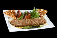 Adana kebab. ı is a long, hand-minced meat kebab mounted on a wide iron skewer and grilled on an open mangal filled with burning charcoal Stock Photography