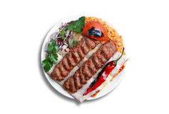 Adana kebab. I, male lamb meat, red bell peppers and tail fat hand minced together. Served with charred peppers and tomatoes, an onion-sumac-parsley salad, and Royalty Free Stock Image