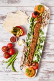 Adana Kebab Served with Green Vegetables in White Plate Stock Images