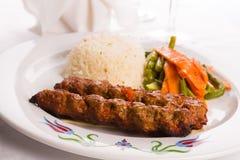 Adana-Kebabs gedient auf einem Lavash-Brot geschmückt mit Gemüse Stockfotografie