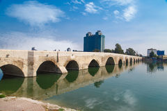 Adana Stone Bridge. Side view of historical old stone bridge of Adana on Seyhan river, on cloudy blue sky background Stock Photography