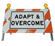 Adapt Overcome Barricade Road Sign Challenge Problem Solving. Adapt and Overcome words on a road construction barricade or sign to illustrate a need to change Royalty Free Stock Photos