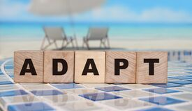 ADAPT Word on wooden blocks standing on swimming pool borders mosaic near the beach. Business change concept