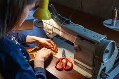 Adaptación de la mujer joven en la máquina de coser foto de archivo