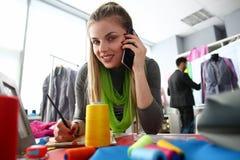 Adaptación del teléfono que habla de la mujer de negocios de la costura fotos de archivo libres de regalías