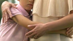 Adaptación social del niño con autismo, muchacho silencioso que abraza a la madre, psicología almacen de video
