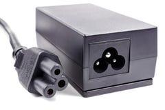 Adaptador de la fuente de alimentación con el cable en un fondo blanco fotos de archivo