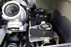 Adaptadores del colector y del fuego del agua del fuego situados en los montajes en un compartimiento del vehículo del fuego Disp imágenes de archivo libres de regalías