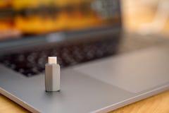 Adapter Gray Thunderbolts USB-C auf der grauen Tastatur auf Laptophintergrund Lizenzfreies Stockfoto