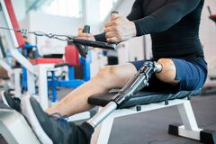 Adaptive Athlete Using Rowing Machine Closeup. Low section closeup of unrecognizable muscular man with prosthetic leg using weight machines while working out in royalty free stock photos