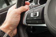 Adaptive cruise control panel buttons. On modern car steering wheel, interior details with driver hand stock photo