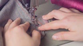 Adattamento del laboratorio artigianale Una giovane cucitrice cuce i vestiti su un tessuto grigio Tonalità, primo piano di uno st immagini stock libere da diritti