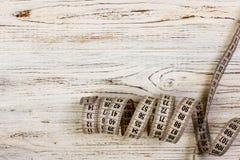Adattamento del nastro di misurazione bianco del tester su fondo di legno fotografie stock libere da diritti