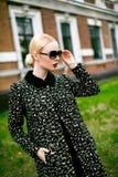 Adatti ad autunno la foto all'aperto di bella donna sexy con capelli ricci scuri che portano un cappotto e talloni e vetri di alt Immagine Stock