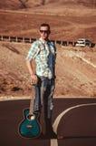 Adatti ad uomo la passeggiata sola sulla strada con la chitarra Fotografia Stock Libera da Diritti