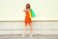 Adatti a donna abbastanza sorridente in vestito rosso con i sacchetti della spesa Fotografia Stock Libera da Diritti