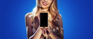 Adatti a foto di stile di una tenuta bionda uno smartphone Fotografia Stock Libera da Diritti