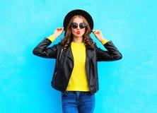 Adatti a giovane donna graziosa i vestiti neri d'uso di uno stile della roccia sopra il blu variopinto Fotografie Stock