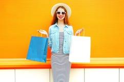 Adatti a giovane donna sorridente con i sacchetti della spesa, cappello di paglia Fotografie Stock Libere da Diritti