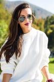 Adatti gli occhiali da sole d'uso del bello ritratto della donna, il maglione bianco e la gonna verde Fotografie Stock