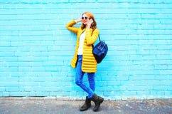 Adatti i colloqui sorridenti della donna su uno smartphone su un mattone blu Immagine Stock
