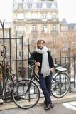 Adatti il modello maschio in vetri di sole rotondi che stanno la bicicletta vicina Fotografie Stock Libere da Diritti