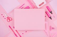Adatti il posto di lavoro alla moda - carta in bianco per testo sulla raccolta rosa al neon della cancelleria dell'ufficio su fon Fotografia Stock