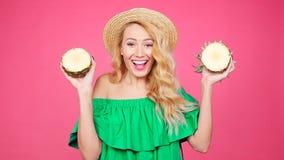 Adatti il ritratto dell'estate di giovane donna graziosa che tiene due grandi ananas dolci stock footage