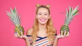 Adatti il ritratto dell'estate di giovane donna graziosa che tiene due grandi ananas dolci video d archivio