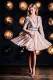 Adatti il ritratto della donna elegante con capelli magnifici Ragazza bionda Trucco perfetto Ragazza in vestito dall'oro su fondo immagine stock