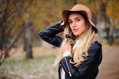 Adatti il ritratto di autunno di giovane camminata felice della donna all'aperto nel parco di caduta Immagine Stock