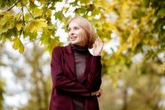 Adatti il ritratto di bella donna bionda in vestiti alla moda nel parco di autunno Fotografie Stock Libere da Diritti