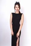 Adatti il ritratto di giovane bella donna in vestito nero lungo Priorità bassa bianca Fotografia Stock Libera da Diritti