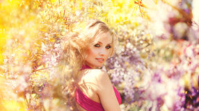 Adatti il ritratto di giovane bella ragazza che posa contro i cespugli lilla in fiore Fotografia Stock