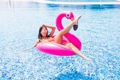 Adatti il ritratto di giovane e ragazza sexy nello stagno su un fenicottero rosa gonfiabile in costume da bagno ed occhiali da so fotografia stock libera da diritti