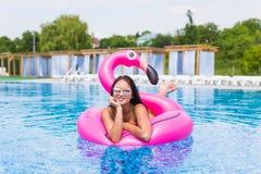 Adatti il ritratto di giovane e ragazza sexy nello stagno su un fenicottero rosa gonfiabile in costume da bagno ed occhiali da so fotografia stock